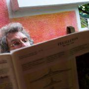 """Grauhaariger Mann mit lockigem Haar blickt über die Zeitung """"DerStandard"""" hervor"""