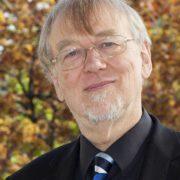 Grauhaariger Mann mit freundlichem Gesicht und Brille