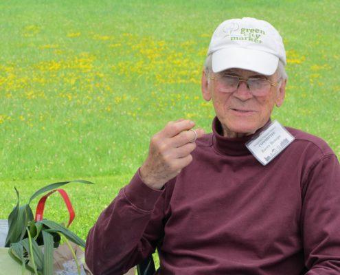 Freundlich schauender alter Mann mit Kappe und Namenskärtchen