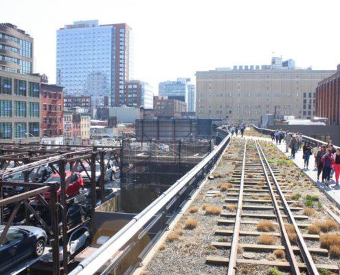 Blick über eine erhöhte alte Eisenbahnlinie, Hochhäuser im Hintergrund