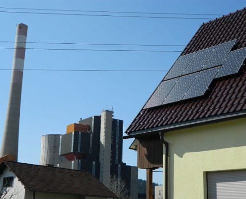 Photovoltaik auf einem Schindeldach, Fabrik im Hintergrund