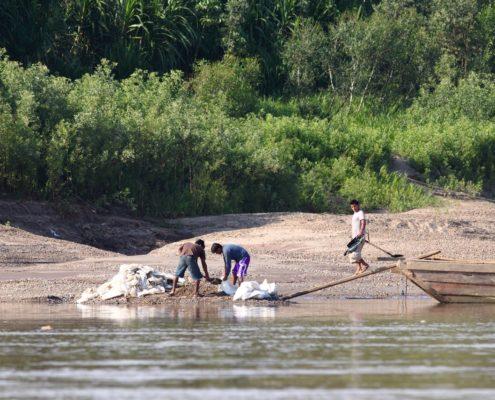 Fluss, im Hintergrund tropische Vegetation, 3 Männer stehen am Flussufer