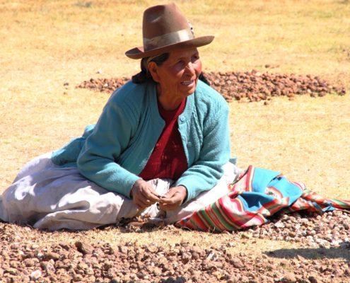 Alte Frau mit sonnengegerbter Haut mit Hut sitzt in farbigem Gewand am Boden