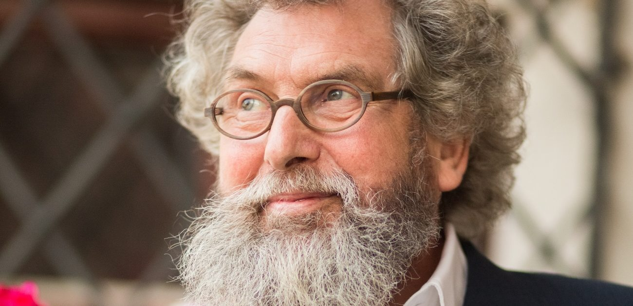Portrait eines gen Himmel blickenden bärtigen Mannes mit lockigem ergrauten Haar und Hornbrille