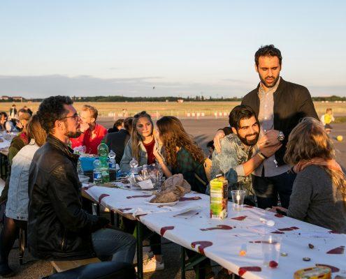 Im Abendlicht sitzen junge Menschen verschiedener Ethnien im Freien an einem Tisch