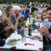 Personen verschiedenster Altersstufen sitzen im Freien an einem Tisch