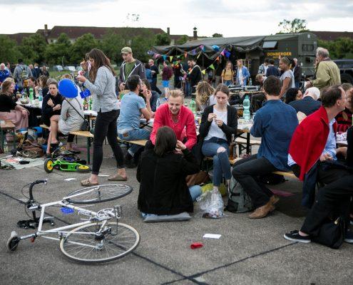 Großes Fest mit Tischen im Freien, Räder liegen am Boden, junge Menschen unterhalten sich