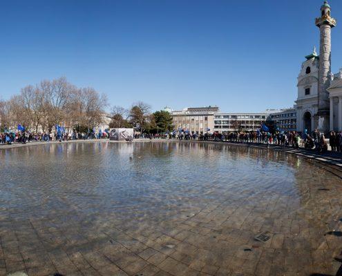 großes künstliches Becken und Menschen stehen rundherum