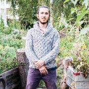 Junger Mann mit langem schwarzen Haar zu Knödel am Kopf zusammengebunden und Bart steht in grauem Pulli und violetter Hose in Garten