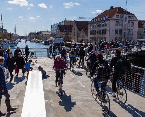 Viele Menschen fahren mit dem Fahrrad durch eine Stadt