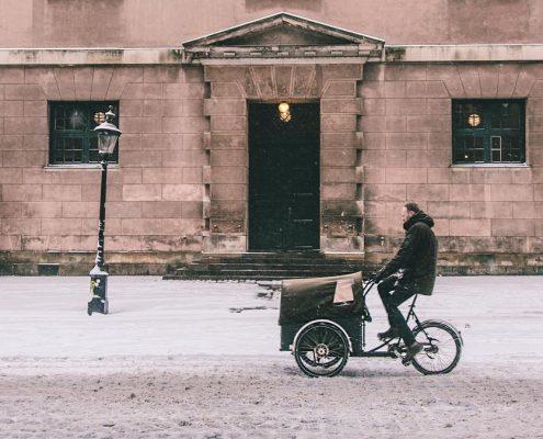 Mann fährt durch leicht schneebedeckte Fahrbarn mit Fahrrad