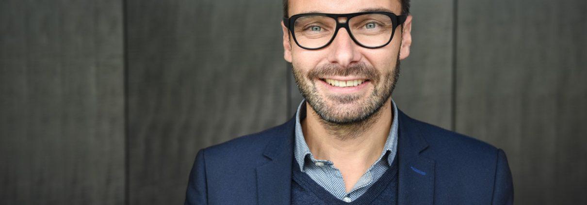 Dunkelhaariger Mann mit 3 Taagebart, dicker Hornbrille und dunkelblauem Anzug lächelt in Kamera
