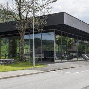 Modernes Gebäude mit viel Glas im Hintergrund schneebedeckte Berge