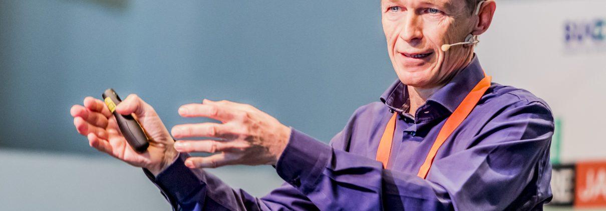 Blonder Mann mittleren Alters in violettem Hemd spricht mit Mikrofon und artikuliert mit den Händen