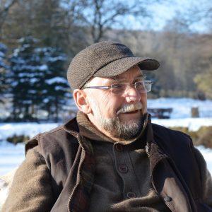 Mann mittleren Alters mit rahmenloser Brille und Bart und Kappe