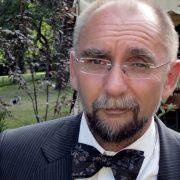 Zynisch blickender Mann mittleren Alters mit leichter Glatze, rahmenloser Brille und Bart in Anzug un Fliege