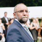 Mann mittleren Alters mit leichter Glatze, rahmenloser Brille und Bart in Anzug
