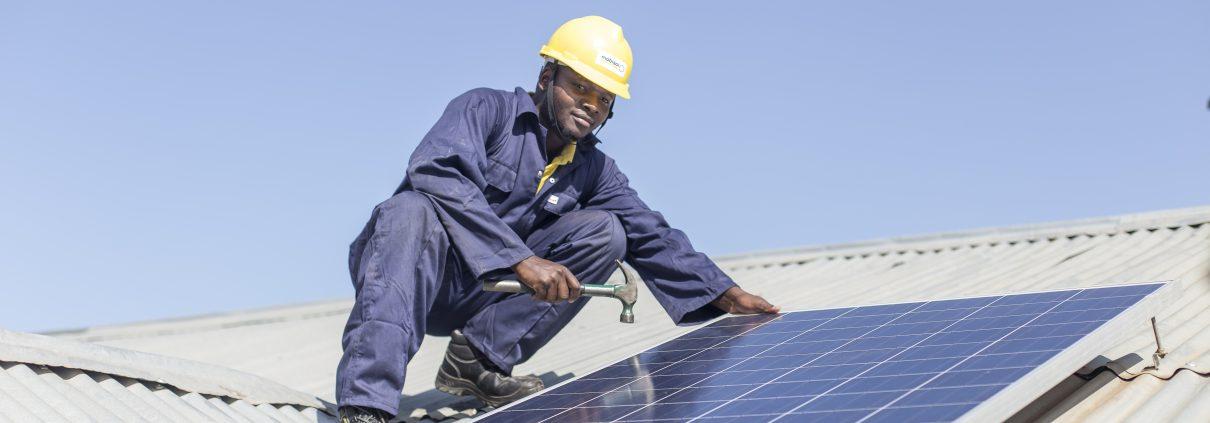 Schwarzer Arbeiter montiert Photovoltaik auf Dach