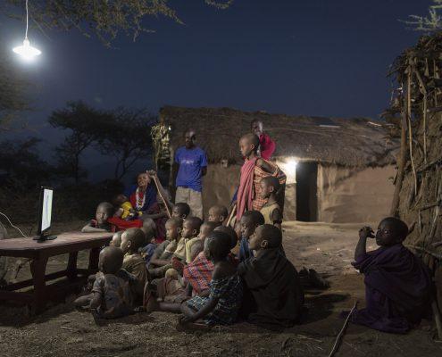 Eine Gruppe schwarzer Kinder sitzt im Freien im Dunkeln vor einem Fernseher