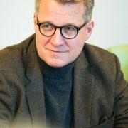 Mann mittleren Alters mit braungrauem Haar und runder Hornbrille