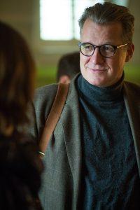 Mann mittleren Alters mit braungrauem Haar und runder Hornbrille mit Ledertasche über der Schulter