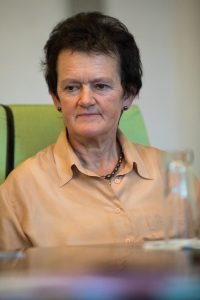 Ernst schauende ältere Frau mit kurzen schwarzen Haaren