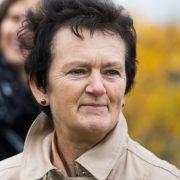 Lächelnde ältere Frau mit kurzem schwarzen Haar im Freien