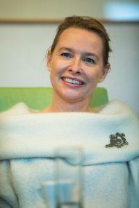 Hübsche blonde lachende Frau in weißem Pullover und großer Brosche