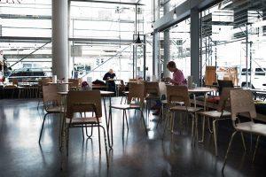 Blick in einen lichtdurchfluteten Raum mit großen Fenstern, vielen Tischen und Sesseln