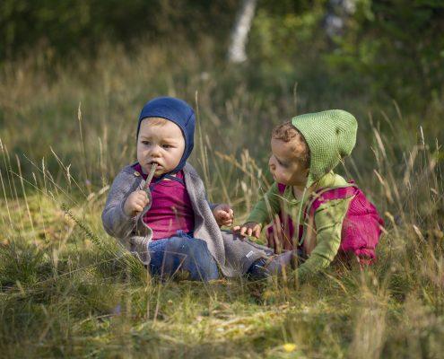2 Kleinkinder hocken in der Wiese