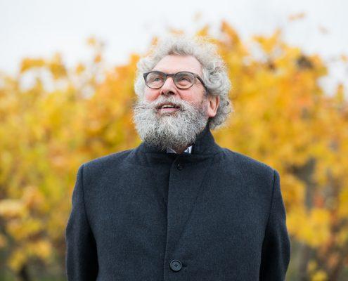 Portrait eines gen Himmel blickenden bärtigen Mannes mit lockigem ergrauten Haar und Hornbrille, im Hintergrund Busch mit gelben Blättern