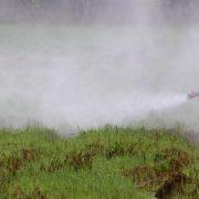 verhüllter Mann sprüht Pestizid auf Feld