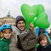 Zwei Kinder, ein Mann und eine Frau stehen vor dem Berliner Tor und halten Herzluftballone in grün mit der Aufschrift AVAAZ