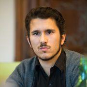 Ernsthaft blickender junger Mann mit schwarzem Haar, dunkelbraunen Augen und getrimmtem Bart