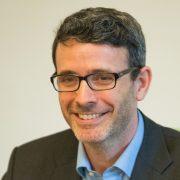 Portrait eines lächelnden Mannes mit leicht grau meliertem Haar, Hornbrille und 3 Tagesbart