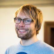 Portrait eines jungen blonden Mannes mit strahlendem Lächeln und Hornbrille