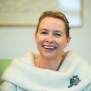 Portrait einer freundlich lachenden blonden Frau mit weißem Pullover und auffalender Brosche