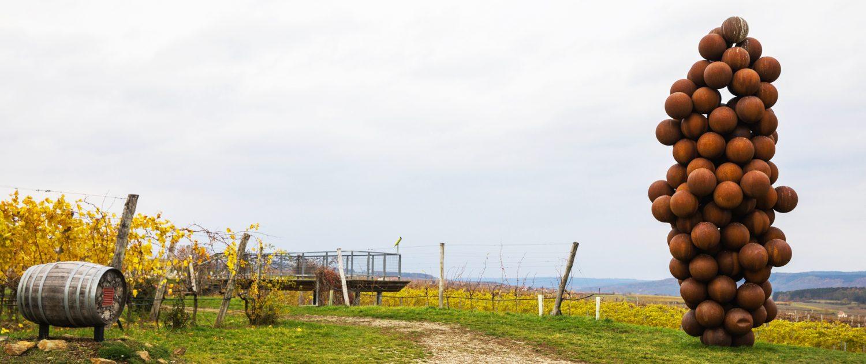 Große Skulptur aus braunen Bällen zusammengesetzt neben einem herbstlichen Weingarten