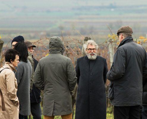 Eine Gruppe von Menschen steht in herbstlicher Landschaft, alle in Mänteln und mit Hauben
