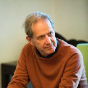 Portrait eines älteren Mannes mit etwas schütterem grauen Haar in dunkelorangem Pullover