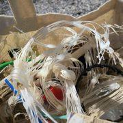 In einem Stoffsack liegt allerhand Plastikmüll