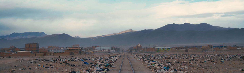 Blick auf hohe Berggipfel, im Vordergrund eine gerade Eisenbahnschiene gesäumt von Plastikmüll