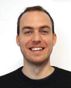 Portrait eines Jungen Mannes mit 3Tages Bart und kurzen dunklen Haaren, der in die Kamera lächelt