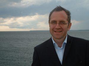 Freundlich lächelnder Mann mit Brille vor Meer stehend