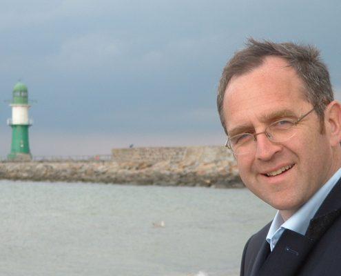 Freundlich lächelnder Mann mit Brille vor Meer und Leuchtturm im Hintergrund