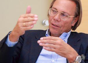 Gestikulierender Mann mit Brille un halblangen Haaren