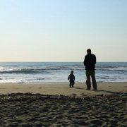 Mann und Kind stehen vor Meer