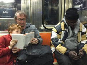 US-Amerikanisch anmutende Ubahn von innen, schwarzer Mann und weißer Mann mit Kind