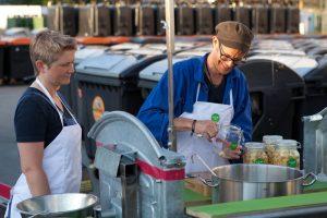 Mann und Frau kochen vor Mülltonnen