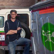 Junger Mann mit Brille und Cappy steht mit verschränkten Armen vor Mülltonne